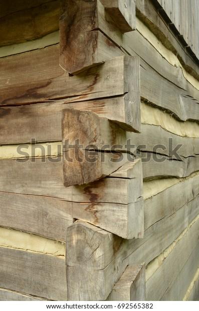 Detail corner of old historic log cabin made of hand-hewn wood