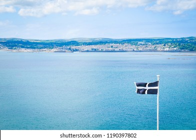 Detail of cornish flag against the blue sea in Marazion, England