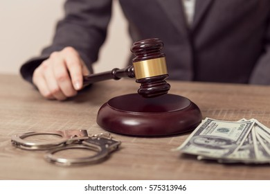 Detail of a corrupted judge holding a gavel and saying the verdict on court. Bribery money and handcuffs on the desk. Selective focus
