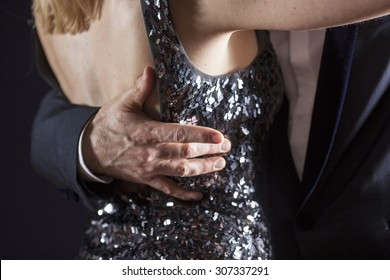 detail of couple ballroom dancing, focus on man's hand on woman's back