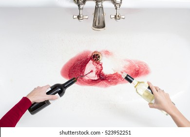Detail of a couple pouring away wine in an act of giving up alcohol