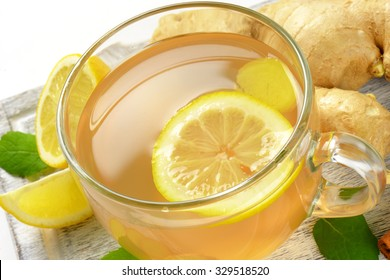 detail of cup of ginger tea with lemon and fresh ginger on wooden cutting board