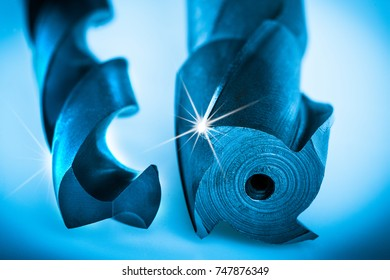 Detail of cutting tools for making geometrically accurate holes. Beautiful drill tools with spiral grooving in blue color with rays on the cutting edge.