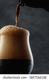 Detail of dark beer with overflowing foam head. Stream of dark stout pours into a beer glass