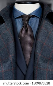 Detail of a dark winter coat in a cage with brown tie and navy blue shirt