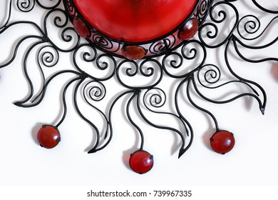 Detail of a decorative moroccan chandelier made of iron and red glass over white background
