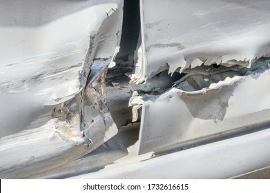 Detail of dented and torn sheet metal on the side of the silver car doors damaged in crash accident.