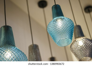 Detail design and interior lighting - white metal lamp. Extreme close-up on the crystal elements of a stylish luxury chandelier. Soft focus and beautiful bokeh.