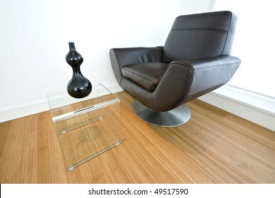Detail of a designer leather armchair with glass coffee table and decorative vase