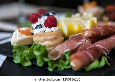 Detail of the dish prepared for an aperitif with breadsticks wrapped in slices of raw ham and tartine with cheese with raspberries and blackberries Turin Italy September 2018