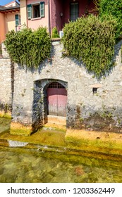 detail of door of old building opening on clear waters in village on shore of Garda lake, shot in bright fall light at Gargnano, Brescia, Italy