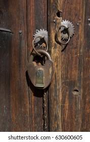 Detail of doorknob and`padlock on wooden doors