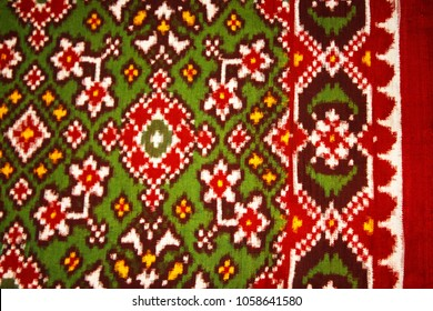 Detail of a Double Ikat weaving in red, green, and white silk thread. Natural vegetable dyes dyes from turmeric, marigolds, onion skins, pomegranate were used. Patan, Gujarat, India