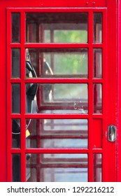 Detail of double red vintage english phone box, many small glass windows at door, view inside through it (copy space)