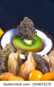 Detail of dried cannabis bud (grandaddy purple strain) with fresh tropical fruit - medical marijuana edible concept