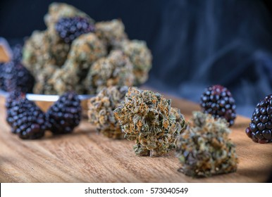 Detail of dried cannabis buds (Berry Noir strain) with fresh fruit - medical marijuana concept background