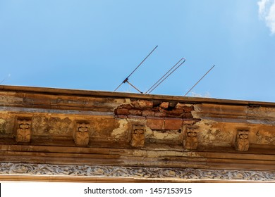 Detail of the eaves of a tile roof. Old eaves boards with blue sky on background.