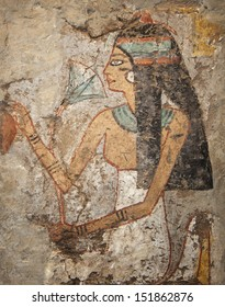 Detail of an Egyptian tomb painting from the New Kingdom (1300-1100 B.C.) of a woman adorning herself with jewelry