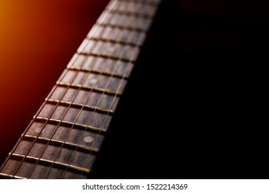detail of the Electric Guitar Fret Board, guitar against a black background