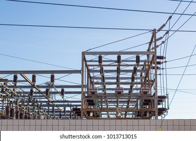 Detail of electric power station behind a block wall, blue sky, horizontal aspect