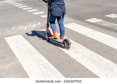 Detail of an electric scooter driven by a woman while waiting her turn to cross a road.