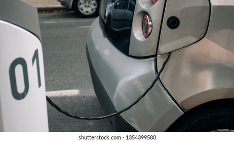 Detail - an electrocar with a charging cord, connecting it to a charger
