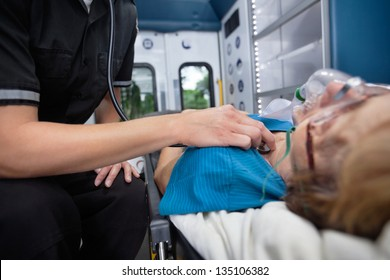 Detail of EMT worker listening to heart of senior woman patient in ambulance