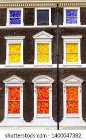 Detail of the external facade of an english town house with windows on classic brick building wall and colored curtains in London, United Kingdom / GB. City views.