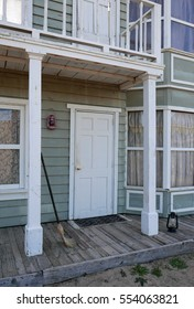 Detail of the facade of an hold house, entrance door, window, bay window and veranda with a broom and a lamp