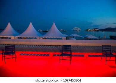 Detail of the famous Croisette promenade in Cannes, France at dusk, with the typical blue chair of the french riviera