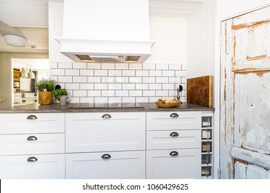 Detail of a fancy kitchen with white cupboards white tile Old rustic door