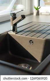 Detail of faucet and sink in contemporary kitchen