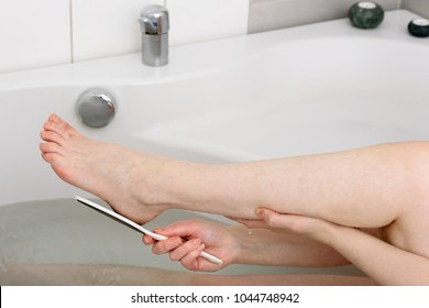 Detail of female giving herself a pedicure in her bathtub. She is using a foot file to rub of dead skin cells from her foot.