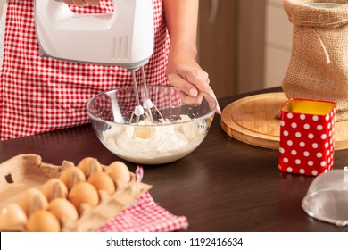Detail of female hand holding mixer and mixing a pancake dough on the kitchen counter. Selective focus on the hand holding the bowl