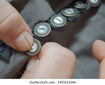 Detail of female hand sewing buttons on clothing