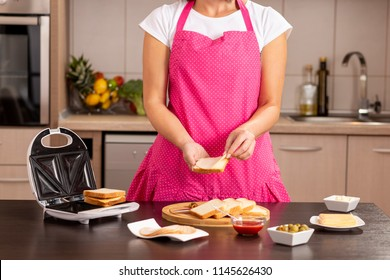 Detail of female hands adding salami on a sandwich; woman making hot sandwiches for breakfast in a sandwich maker