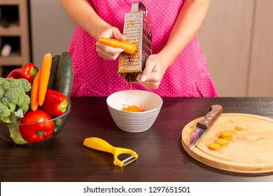 Detail of female hands grating fresh carrots with a grater on a kitchen counter for making fresh vegetable salad