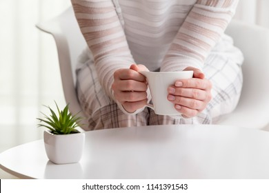 Detail of female hands holding a cup of fresh hot coffee; woman in a pajamas enjoying her morning coffee