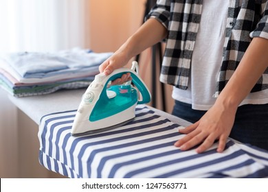 Detail of female hands holding the iron, ironing washed, wrinkled clothes on the ironing board. Selective focus on the thumb and the iron