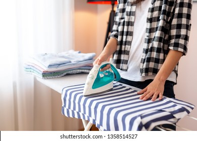Detail of female hands holding the iron, ironing washed, wrinkled clothes on the ironing board
