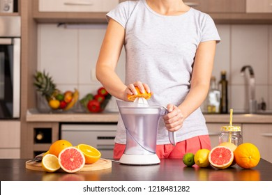 Detail of female hands holding an orange half and making a freshly squeezed mixed citrus fruit with the help of a citrus juicer