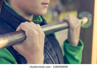 Detail of female hands holding a pullup bar at outdoor fitness.
