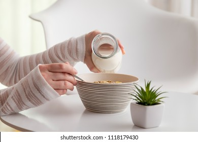 Detail of female hands pouring milk into a bowl of cereals; woman having breakfast. Focus on the cereal and the tip of the bottle