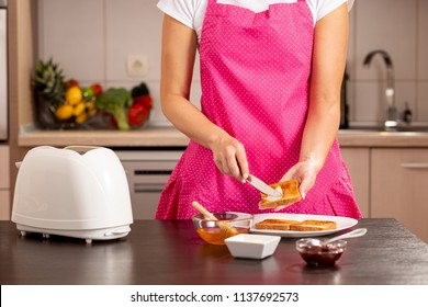Detail of female hands spreading butter over a toasted bread slice, making a sandwich for breakfast. Selective focus on the knife and the hands