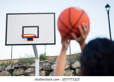 Detail of female hands throwing the ball to the hoop. Basketball play concept.