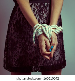 Detail of female hands tied up with rope