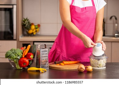 Detail of female hands turning on an onion chopper on the kitchen counter; woman making lunch in the kitchen, chopping onions