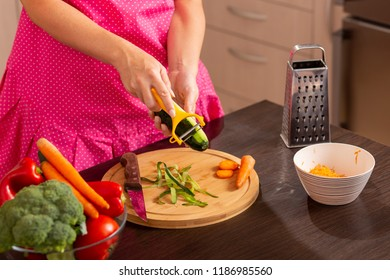 Detail of female hands using a cucumber slicer in order to peel a cucumber for making a fresh vegetable salad