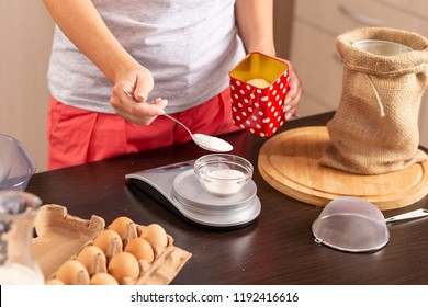 Detail of female hands using a kitchen scale for measuring sugar; woman measuring ingredients for making a cake. Focus on the spoon