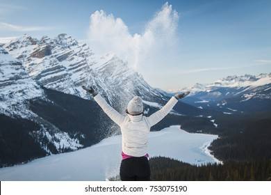 Detail of female outdoor enthusiast throwing, spreading snow in shape of heart at viewpoint above Peyto Lake, Alberta, Canada, Banff National Park. Winter outdoor activities in Rockies, love, joy.